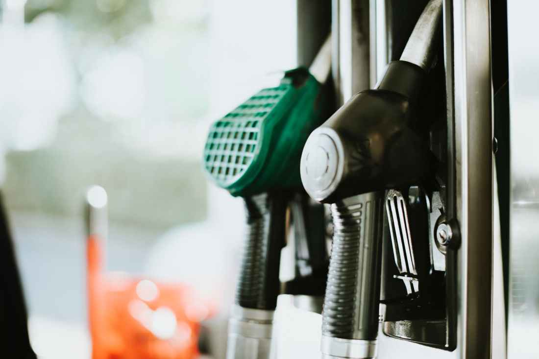 selective focus photography of gasoline nozzle